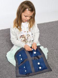 Montessori-Material: Übungwfeld zum Knöpfe öffnen und sschließen.